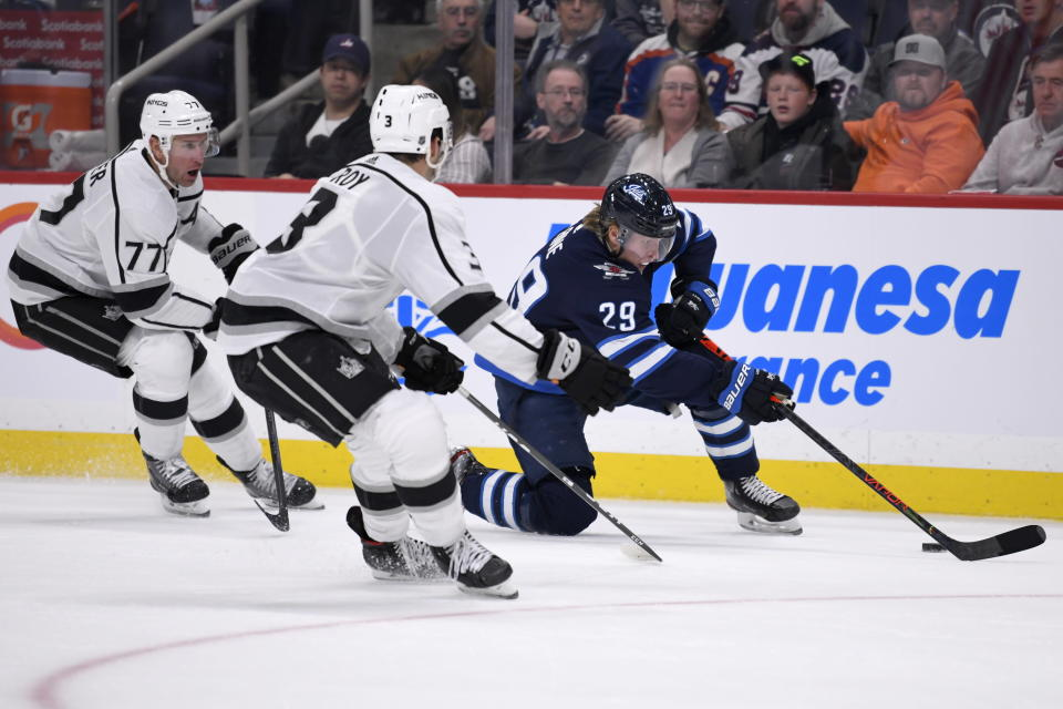 Winnipeg Jets' Patrik Laine (29) carries the puck past Los Angeles Kings' Jeff Carter (77) and Matt Roy (3) during the second period of an NHL hockey game Tuesday, Oct. 22, 2019, in Winnipeg, Manitoba. (Fred Greenslade/The Canadian Press via AP)
