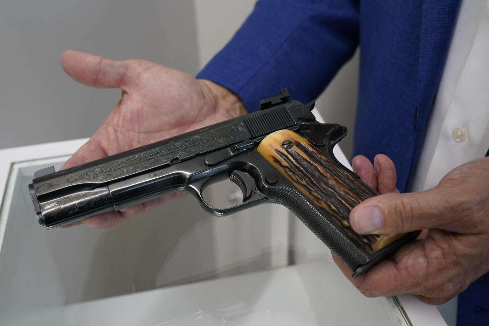 """Brian Witherell displays a Colt .45-caliber pistol that once belonged to mob boss Al Capone, at Witherell's Auction House in Sacramento, Calif., Wednesday, Aug. 25, 2021. The pistol is among the 174 family heirlooms that will be up for sale at an Oct. 8 auction titled """"A Century of Notoriety: The Estate of Al Capone,"""" that will be held by Witherell's. (AP Photo/Rich Pedroncelli)"""