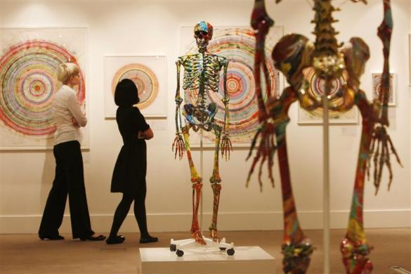 Visitors walk through a gallery containing works by Damien Hirst, collectively entitled 'Beautiful Inside My Head Forever,' at Sotheby's in London on September 8, 2008.