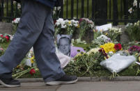 A man walks past a photo of Britain's Prince Philip among flowers left by the public outside the gates of Windsor Castle, a day after the death of Britain's Prince Philip, in Windsor, England, Saturday, April 10, 2021. Britain's Prince Philip, the irascible and tough-minded husband of Queen Elizabeth II who spent more than seven decades supporting his wife in a role that mostly defined his life, died on Friday. (AP Photo/Frank Augstein)