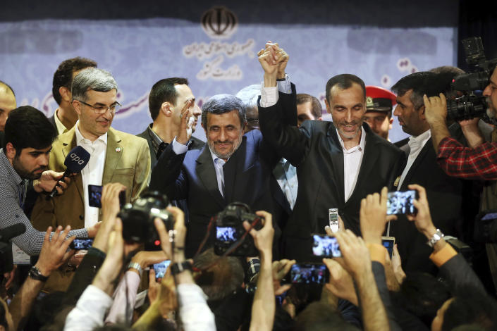 Former Iranian President Mahmoud Ahmadinejad, center, and his close ally Hamid Baghaei join hands after registering their candidacy for the upcoming presidential elections at the Interior Ministry to , in Tehran, Iran, Wednesday, April 12, 2017. Ahmadinejad on Wednesday unexpectedly filed to run in the country's May presidential election, contradicting a recommendation from the supreme leader to stay out of the race. Other close ally of Ahmadinejad, Esfandiar Rahim Mashie accompanies them. (AP Photo/Ebrahim Noroozi)