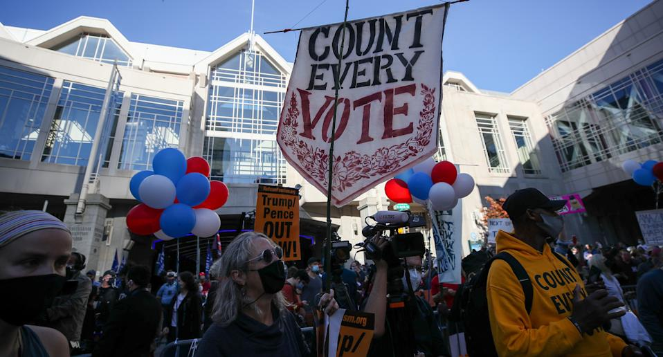 """A sign saying """"Count Every Vote"""" was seen among a crowd of supporters."""