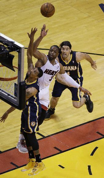 Miami Heat guard Dwyane Wade (3) drives to the basket as Indiana Pacers guard George Hill, left, and Indiana Pacers forward Luis Scola (4) defend, during the first half of Game 4 in the NBA basketball Eastern Conference finals playoff series, Monday, May 26, 2014, in Miami. (AP Photo/Lynne Sladky)