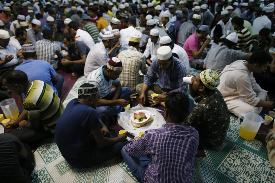 Devotees break fast on the first day of Ramadan at a mosque in Singapore in this June 29, 2014 file photo. Halal has never looked so good for Singapore. A survey ranked the Asian country as the top non-Islamic destination for Muslim tourists, weeks after official data showed overall visitor numbers fell last year for the first time since 2009. REUTERS/Edgar Su/Files (SINGAPORE - Tags: FOOD RELIGION)