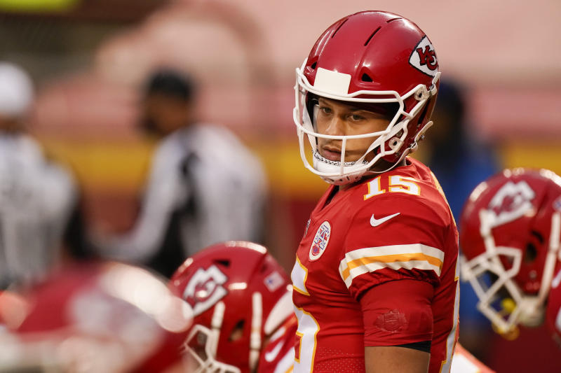 Kansas City Chiefs quarterback Patrick Mahomes behind center looks back.