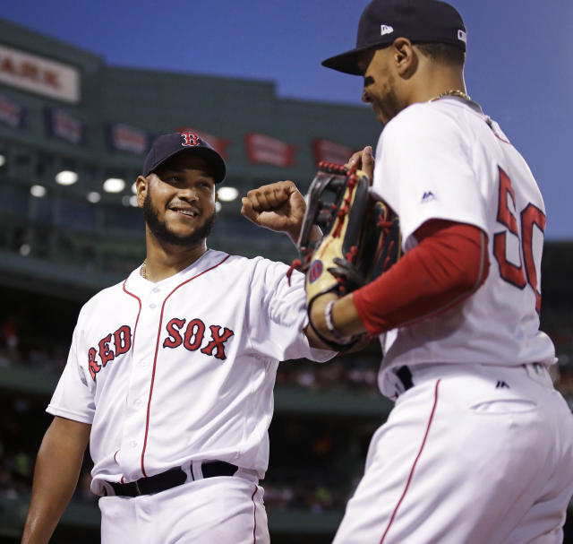 Boston Red Sox starting pitcher Eduardo Rodriguez, left, congratulates center fielder Mookie Betts, right, after Betts' leaping catch on a drive by Texas Rangers Elvis Andrus, which ended the top of the fifth inning, during a baseball game against the Boston Red Sox at Fenway Park in Boston, Monday, July 9, 2018. (AP Photo/Charles Krupa)