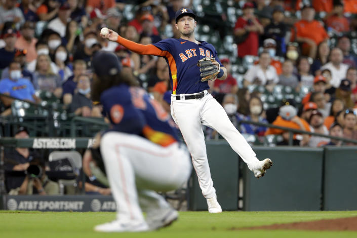 Houston Astros third baseman Alex Bregman throws to first base over pitcher Lance McCullers Jr. for an out against Los Angeles Angels' Kurt Suzuki during the fifth inning of a baseball game Sunday, Sept. 12, 2021, in Houston. (AP Photo/Michael Wyke)