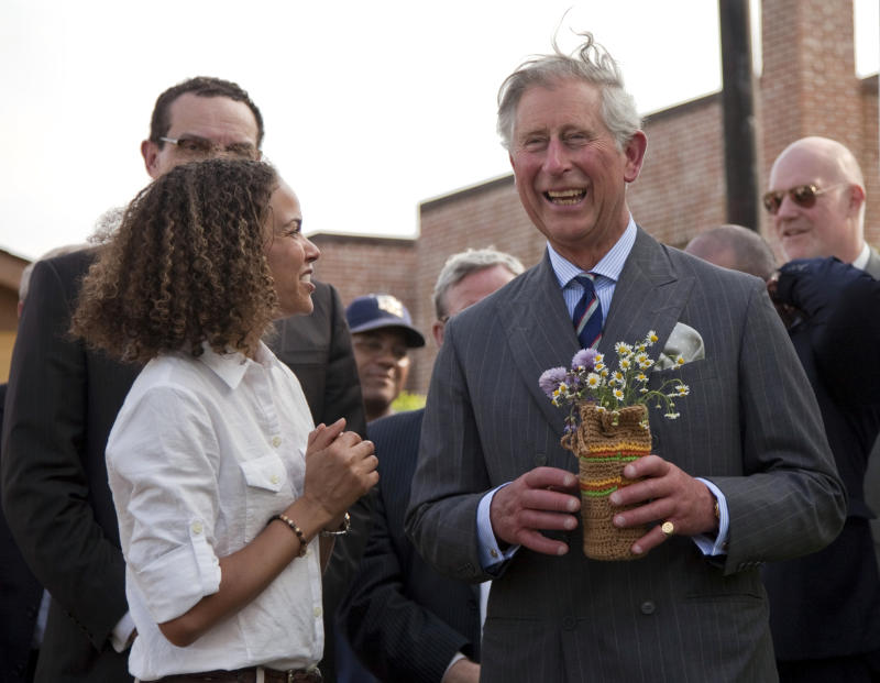 Britain's Prince Charles smiles after he was given flowers by Pertula George, left, during a tour of the Common Good City Farm on Capitol Hill on Tuesday, May 3, 2011, in Washington.  (AP Photo/Evan Vucci)