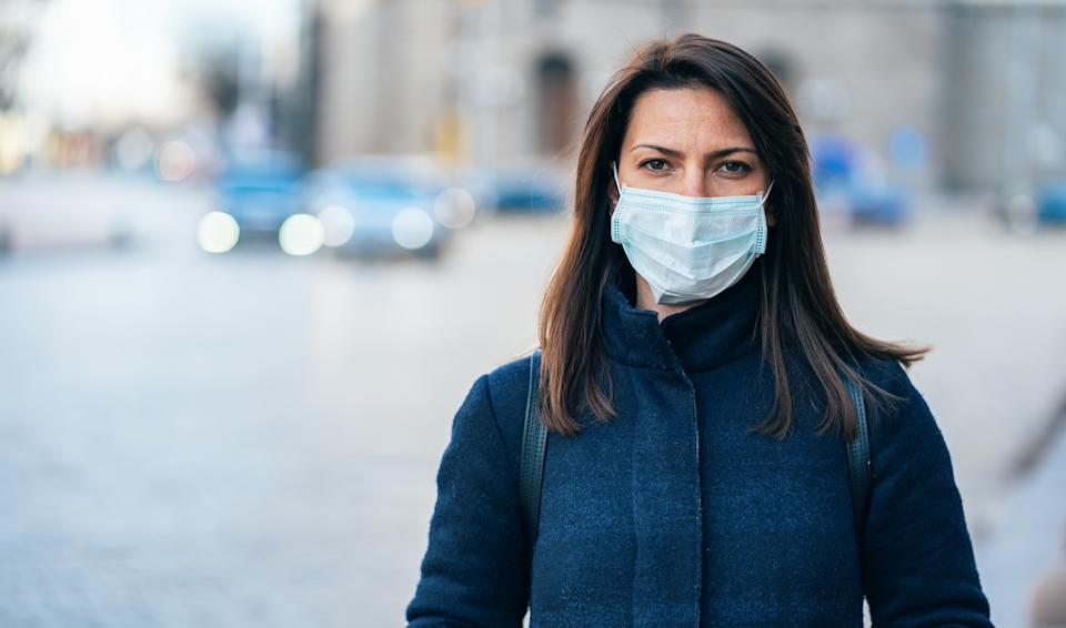 Portrait of young woman on the street wearing  face protective mask to prevent Coronavirus and anti-smog