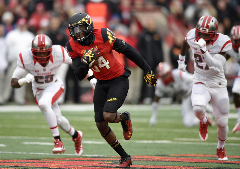 Maryland wide receiver Amba Etta-Tawo (84) runs past Rutgers defensive back Delon Stephenson, right, and Davon Jacobs, left, en route to scoring on a 71-yard touchdown play during the first half of an NCAA college football game, Saturday, Nov. 29, 2014, in College Park, Md. (AP Photo/Nick Wass)