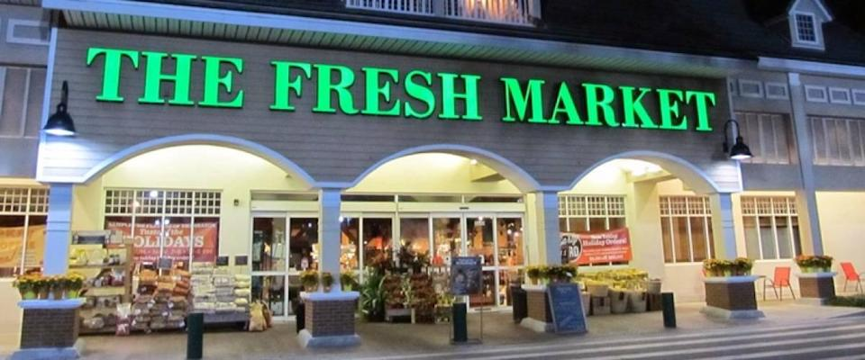 Storefront of the Fresh Market store at night.