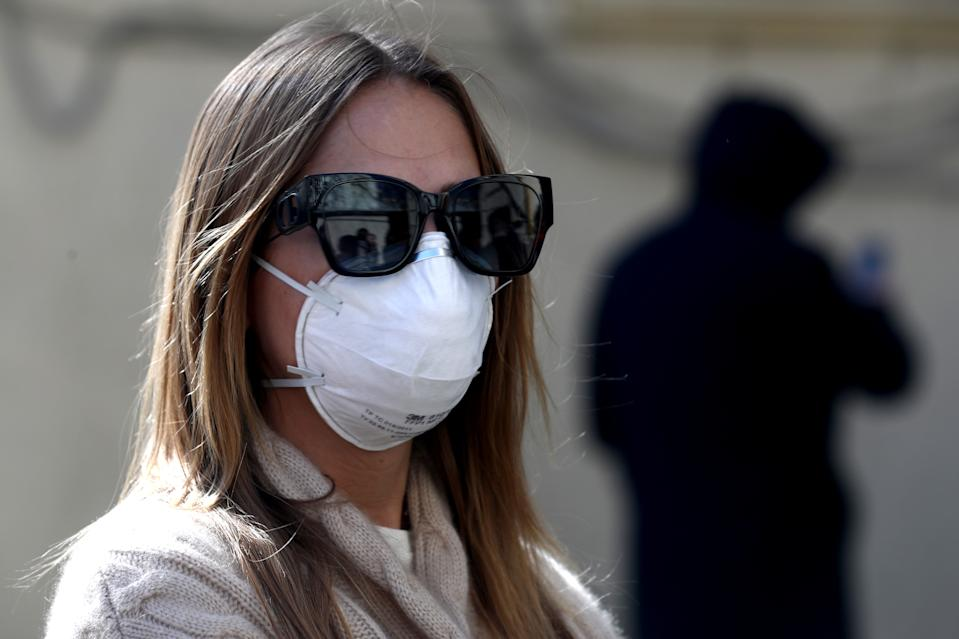 MOSCOW, RUSSIA - MARCH 26, 2020: A girl in a face mask by the entrance to a Gemotest lab that has launched paid testing for SARS-CoV-2, a positive-sense single-stranded RNA virus, the cause of the ongoing COVID-19 pandemic. Stanislav Krasilnikov/TASS (Photo by Stanislav Krasilnikov\TASS via Getty Images)