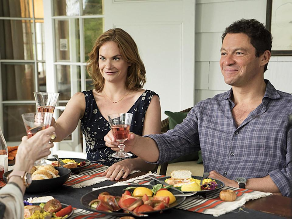 Ruth Wilson and Dominic West cheers glasses at a table