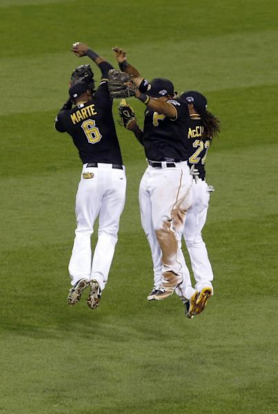 Pittsburgh Pirates left fielder Starling Marte (6) leaps with center fielder Andrew McCutchen, right, and right fielder Marlon Byrd in celebration after defeating the Cincinnati Reds in the NL wild-card playoff baseball game on Tuesday, Oct. 1, 2013, in Pittsburgh. The Pirates won 6-2 and advance to the National Legue Division Series.(AP Photo/Keith Srakocic)