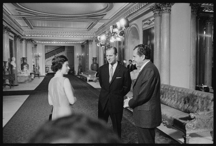 In this undated image provided by The Richard Nixon Library & Museum, Queen Elizabeth II and her husband Prince Philip talk with U.S. President Richard Nixon at Buckingham Palace in London. / Credit: The Richard Nixon Library & Museum via AP