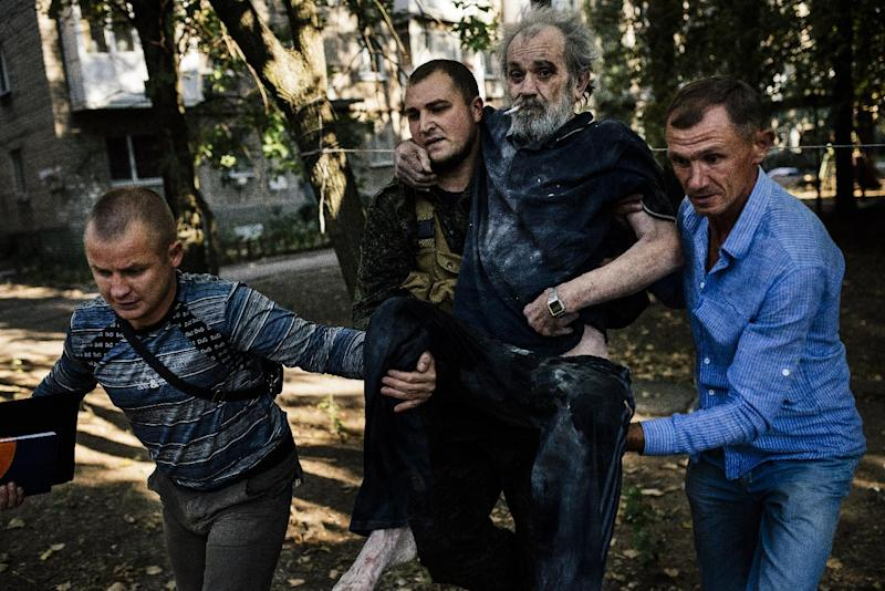 Men carry a wounded elderly man after a shelling in the main separatist stronghold Donetsk, Ukraine on August 23, 2014