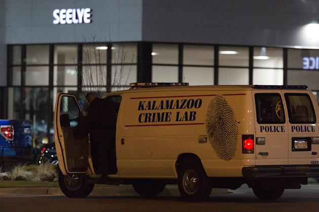 CLICK IMAGE for slideshow: An officer with the Kalamazoo Crime Lab leaves the scene of a random shooting on Sunday in Kalamazoo. Jason Dalton of Kalamazoo County was arrested early Sunday in downtown Kalamazoo following a massive manhunt after several victims were shot at random. (Bryan Bennett/Kalamazoo Gazette-MLive via AP)
