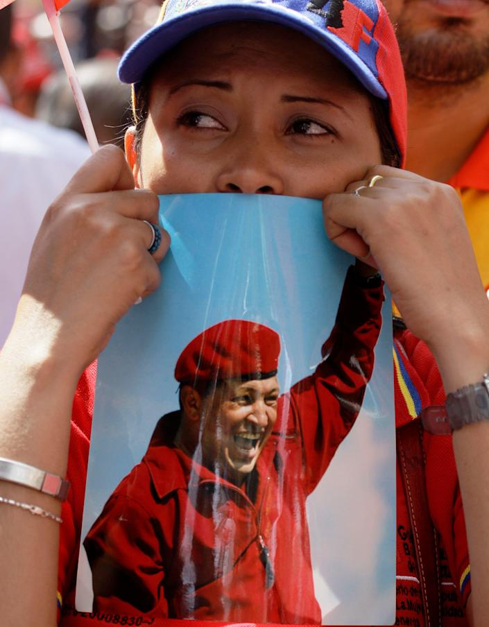 """A woman holds a picture of Venezuela's President Hugo Chavez during an event commemorating the violent street protests of 1989 known as the """"Caracazo,"""" in Caracas, Venezuela, Wednesday, Feb. 27, 2013. The wave of the 1989 violent protests, seen by the Chavez government as a """"popular uprising,"""" was in response to the economic measures imposed by then President Carlos Andres Perez. (AP Photo/Fernando Llano)"""