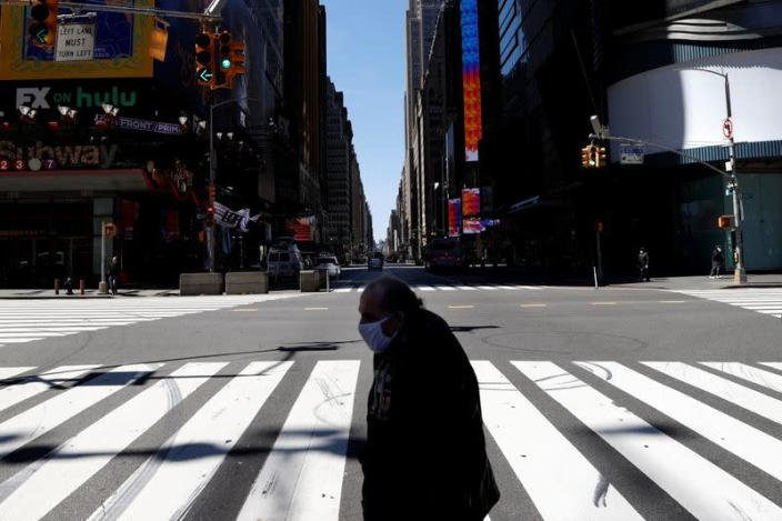 A man crosses 7th Avenue in nearly deserted Times Square during the outbreak of the coronavirus disease (COVID-19) in New York