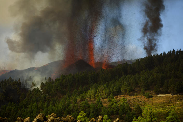 Lava flows from an eruption of a volcano at the island of La Palma in the Canaries, Spain, Sunday, Sept. 19, 2021. A volcano on Spain's Atlantic Ocean island of La Palma erupted Sunday after a weeklong buildup of seismic activity, prompting authorities to evacuate thousands as lava flows destroyed isolated houses and threatened to reach the coast. New eruptions continued into the night. (AP Photo/Jonathan Rodriguez)