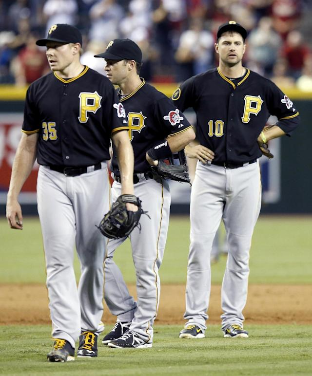 Dismayed Pittsburgh Pirates' Mark Melancon (35), Jayson Nix, and Jordy Mercer (10) look around, as a ball was deflected on a second base play allowing the winning Arizona Diamondbacks run to score during the 10th inning of a baseball game on Sunday, Aug. 3, 2014, in Phoenix. The Diamondbacks defeated the Pirates 3-2. (AP Photo/Ross D. Franklin)