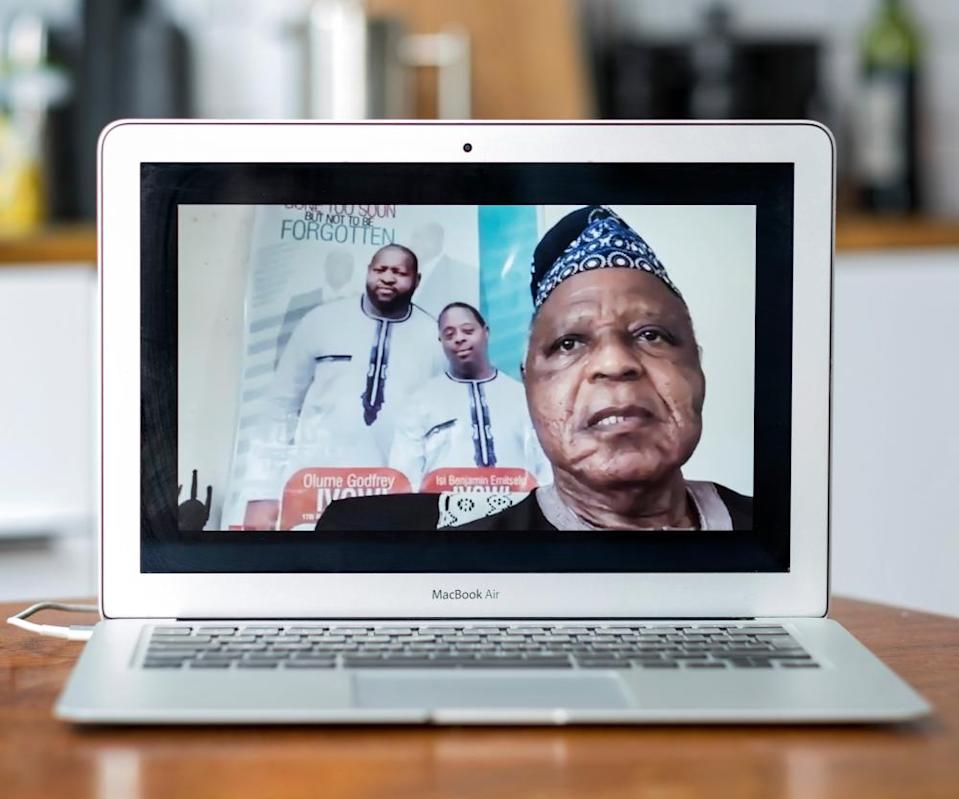 A Zoom portrait of Sir Oyaseh Ivowi; behind him is a poster of two of his sons, Olume (left) and Isi.