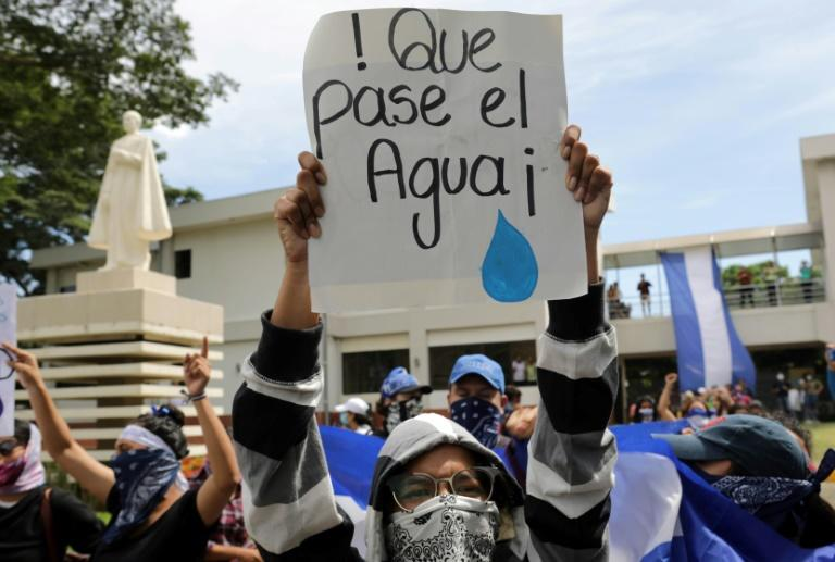 """A protester carries a sign reading """"Let the water pass"""" during a demonstration by students and relatives of political prisoners in Managua"""