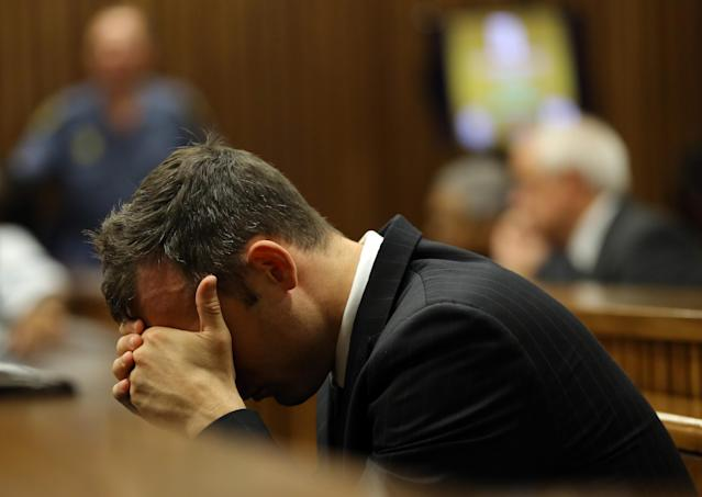 Oscar Pistorius places his head in his hands as he listens to the cross examination during his trial in court in Pretoria, South Africa, Thursday March 13, 2014. Pistorius is charged with the shooting death of his girlfriend Reeva Steenkamp on Valentines Day in 2013. (AP Photo/Themba Hadebe, Pool)