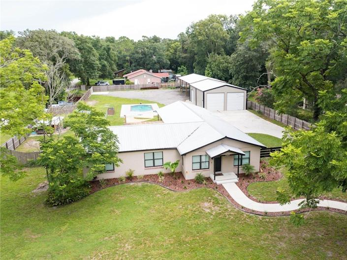 aerial view of a house for sale in florida with detached garage and pool in the background