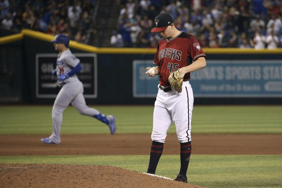 Arizona Diamondbacks relief pitcher Taylor Clarke, right, looks at a new baseball after giving up a home run against Los Angeles Dodgers' Joc Pederson, left, during the 11th inning of a baseball game Sunday, Sept. 1, 2019, in Phoenix. The Dodgers defeated the Diamondbacks 4-3. (AP Photo/Ross D. Franklin)