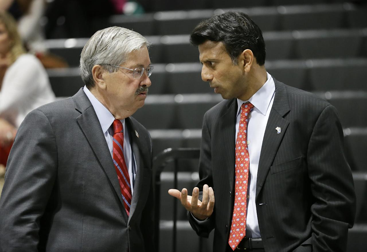Louisiana Gov. Bobby Jindal, right, talks with Iowa Gov. Terry Branstad during the Iowa State Republican Convention, Saturday, June 14, 2014, in Des Moines, Iowa. (AP Photo/Charlie Neibergall)