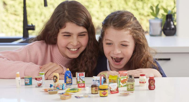 Two girls pictured looking over the new range of Coles Little Shop 2 collectables.