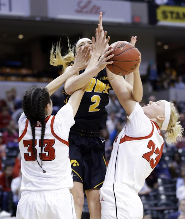 Iowa guard Ally Disterhoft (2) is fouled by Nebraska guard Rachel Theriot (33) and forward Emily Cady in the first half of an NCAA college basketball game in the finals of the Big Ten women's tournament in Indianapolis, Sunday, March 9, 2014. (AP Photo/Michael Conroy)