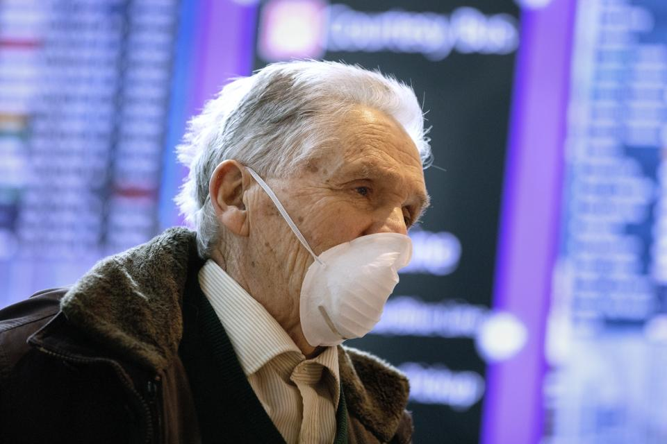 A passenger who arrived on a flight from Germany stands in front of a flight information board at Logan International Airport in Boston, Friday, March, 13, 2020. Beginning at midnight Friday most Europeans will be banned from entering the United States for 30 days to try to slow down the spread of the coronavirus. Americans returning from Europe will be subject to enhanced health screening. For most people, the new coronavirus causes only mild or moderate symptoms, such as fever and cough. For some, especially older adults and people with existing health problems, it can cause more severe illness, including pneumonia. The vast majority of people recover from the new virus. (AP Photo/Michael Dwyer)