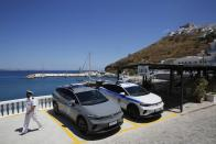 Volkswagen ID.4 electric cars of the Coast Guard and Police are parked on the Aegean Sea island of Astypalea, Greece during the official launch of a project to introduce and test electric vehicles and sustainable energy systems on Wednesday, June 2, 2021. The government has partnered with the German carmaker on the island project aimed a switching to electric vehicle use over the next five years. (Alexandros Vlachos/Pool via AP)