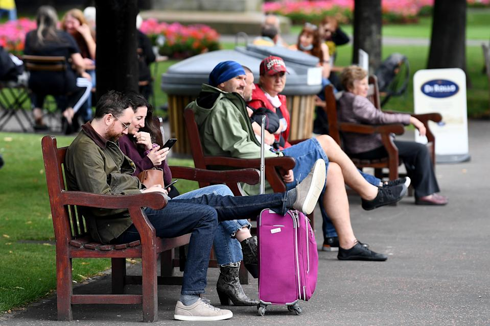 EDINBURGH, SCOTLAND - SEPTEMBER 14: Members of the public sit on park benches as a new law comes into force limiting social gatherings to a maximum of six people from two households on September 14, 2020 in Edinburgh, Scotland. The country joined England in imposing a six-person limit on indoor and outdoor gatherings to curb a rise in Covid-19 infections. (Photo by Jeff J Mitchell/Getty Images)