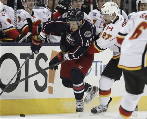 Columbus Blue Jackets' Artem Anisimov, left, of Russia, works for the puck against Calgary Flames' Derek Smith in the second period of an NHL hockey game in Columbus, Ohio, Friday, March 22, 2013. (AP Photo/Paul Vernon)