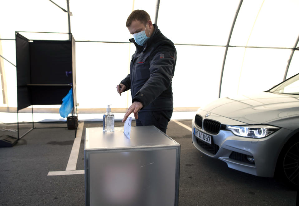 A voter, wearing face masks to protect against coronavirus casts his ballot on the first day of early voting in the second round of a parliamentary election at a drive-in polling station, special place of advance voting for self isolated voters in Vilnius, Lithuania, Monday, Oct. 19, 2020. Lithuanians are voting in the second round of a parliamentary election on Sunday during the rise in the incidence of coronavirus infection in the country. (AP Photo / Mindaugas Kulbis)