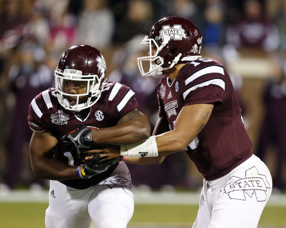Mississippi State quarterback Dak Prescott (15) hands off to running back Josh Robinson (13) in the first half of an NCAA college football game in Starkville, Miss., Saturday, Nov. 1, 2014. No. 1 Mississippi State won 17-10. (AP Photo/Rogelio V. Solis)