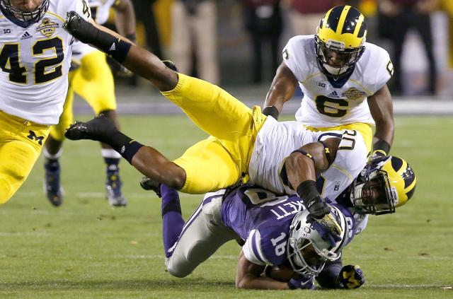Kansas State's Tyler Lockett (16) is tackled by Michigan's Thomas Gordon (30) as Michigan's Raymon Taylor (6) looks on during the first half of the Buffalo Wild Wings Bowl NCAA college football game on Saturday, Dec. 28, 2013, in Tempe, Ariz. (AP Photo/Ross D. Franklin)