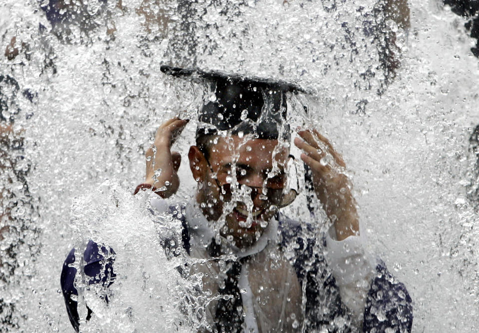 A New York University student celebrates in the Washington Square Park fountain after the 175th NYU Graduation Ceremony in New York City in this May 10, 2007 archive photo. To some academics, the financial crisis is the ultimate