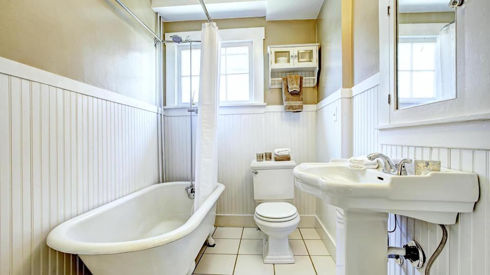 Claw foot tub in bright bathroom with white wall trim, washbasin stand and toilet.