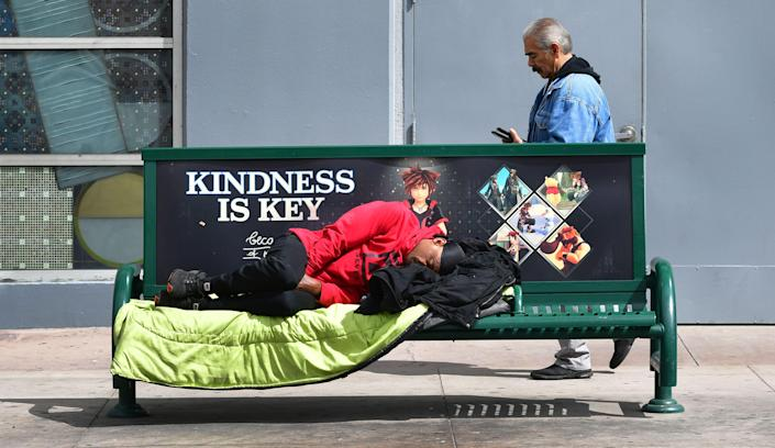 A man sleeps on bench near a bus stop in Los Angeles, California on March 17, 2020. - Cities across the nation are worried about the homeless population as the coronavirus pandemic surges with the US death toll reaching 100. (Photo by Frederic J. BROWN / AFP) (Photo by FREDERIC J. BROWN/AFP via Getty Images)