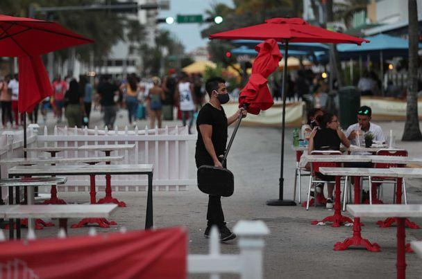 PHOTO: A worker at the Boulevard Hotel restaurant carries an umbrella in the outdoor seating area of a restaurant in Miami Beach, Fla., July 18, 2020. (Joe Raedle/Getty Images)