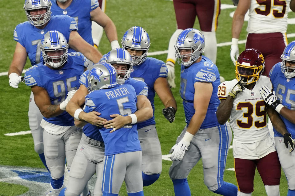 Teammates hug Detroit Lions kicker Matt Prater (5) after his winning field goal in the closing seconds during the second half of an NFL football game against the Washington Football Team, Sunday, Nov. 15, 2020, in Detroit. (AP Photo/Carlos Osorio)