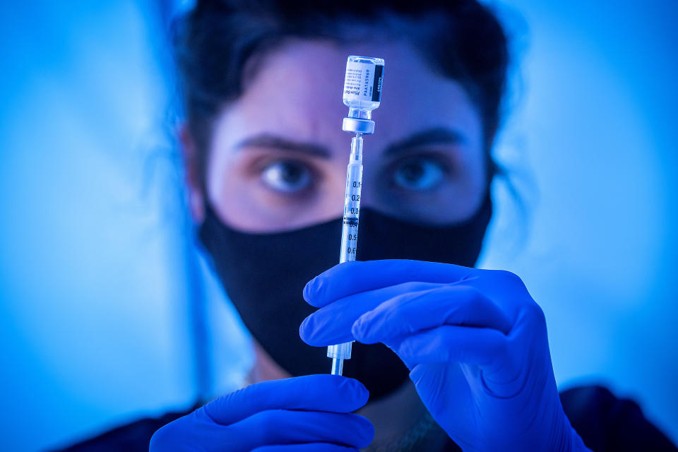 Getting the COVID-19 vaccine, seen here being readied by a medical student in Los Angeles recently, can help COVID long-haulers feel better, according to anecdotal evidence. (Photo: Allen J. Schaben / Los Angeles Times via Getty Images)