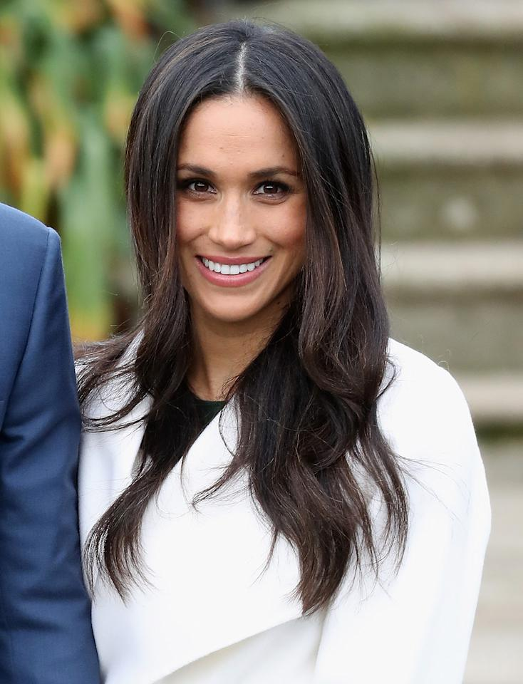 <p>At the official photo call to announce her engagement to Prince Harry, the 36-year-old smiled joyfully wearing long, luxurious layers. (Photo: Chris Jackson/Getty Images) </p>