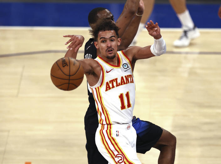 Atlanta Hawks' Trae Young (11) passes the ball as New York Knicks' Alec Burks defends during the fourth quarter in Game 2 in an NBA basketball first-round playoff series Wednesday, May 26, 2021, in New York. (Elsa/Pool Photo via AP)