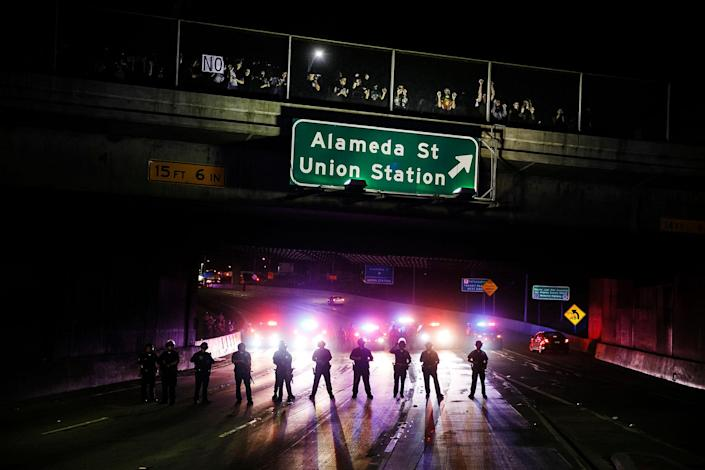 <p>Police officers stand guard as they slowly clear anti-Trump protesters off the 101 freeway, in Los Angeles, Calif., on Nov. 10, 2016. (Photo: Marcus Yam/Los Angeles Times via Getty Images) </p>