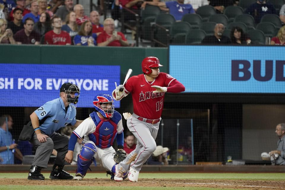 Los Angeles Angels' Shohei Ohtani follows through on a ground out to second as Texas Rangers' Jose Trevino and umpire Mike Muchlinski looks on in the seventh inning of a baseball game in Arlington, Texas, Wednesday, Sept. 29, 2021. (AP Photo/Tony Gutierrez)